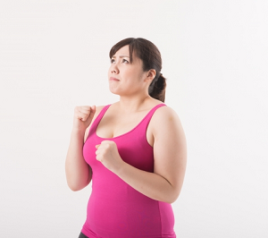 顔の脂肪を減らそうと意気込む女性の画像