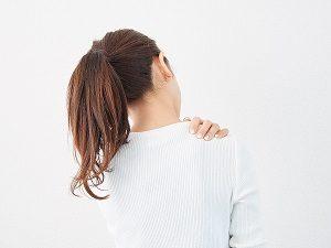 筋肉の過緊張で肩が凝っている女性の画像