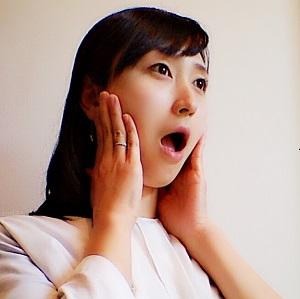 耳下腺を押さえながら口を開閉している画像